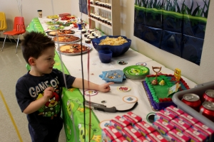Cole checking out the birthday cake and bird launcher